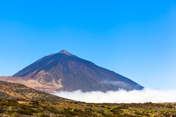 Tall Mountain Rock and Sky / View to Teide mountain above clouds at national park on Tenerife island, blue sky copy space