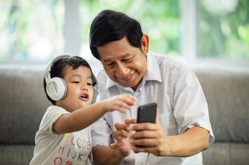 Happiness Asia grandfather  and grandson playing game in living room at home