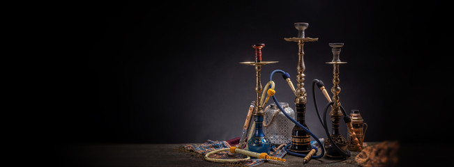 Rustic handmade hookah and arabic tea for relaxation in a dark moody room, rustic decoration, smoke and shisha components