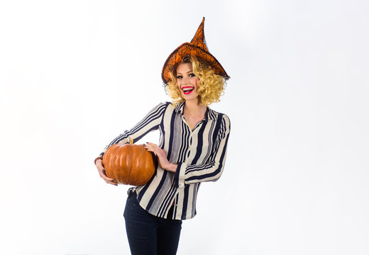 Halloween woman with happy face. Woman in witch hat holds pumpkin. Girl with orange pumpkin. Holiday and celebration. Happy Halloween Quotes and Sayings. Halloween party. Traditional food. Magic hat.