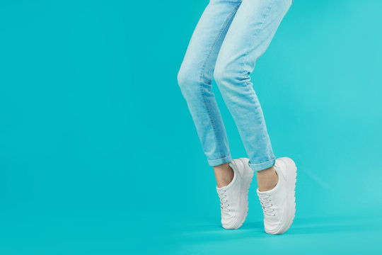 Woman in stylish sport shoes on light blue background. Space for text