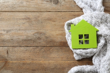 House model and scarf on wooden background, top view with space for text. Heating efficiency
