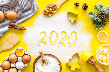 Happy New Year concept. 2020 written on yellow baking background top view