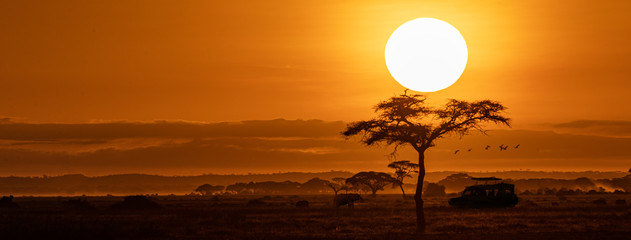 Fotobehang Afrika Orange Sunset Safari Vehicle Horizontal Web Banner
