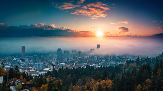 Portland downtown with rolling fog and autumn foliage in shining sunrise and colorful clouds