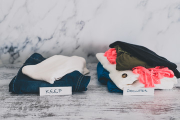 declutter and tidying up fashion clothes stacked into Keep and Declutter piles with text