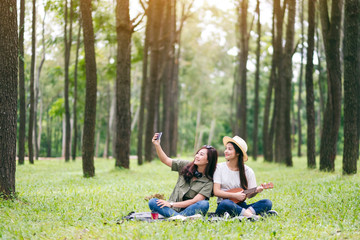 Two women taking selfie while playing ukulele together in the woods