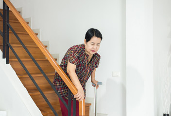 Elderly asian woman holding sticks while walking down stair at home