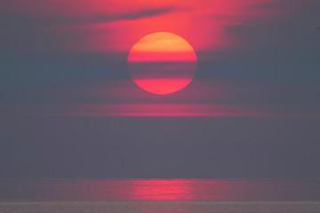 Closeup sunrise over water, large red orange sun, birds  flying