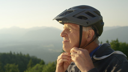 CLOSE UP: Focused senior man straps up his helmet before an evening bicycle ride