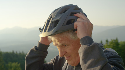 CLOSE UP: Older man puts on a helmet before a bicycle ride on a sunny evening.