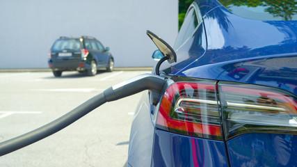 CLOSE UP: Detailed shot of a shiny new Tesla car recharging at a parking lot.
