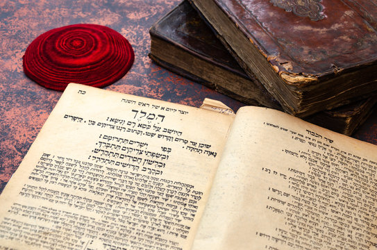 Jewish Bible. A stack of old leather-bound Jewish books with gold stamping and red knitted jewish bale. One book is open. Closeup of Hebrew text. Selective focus