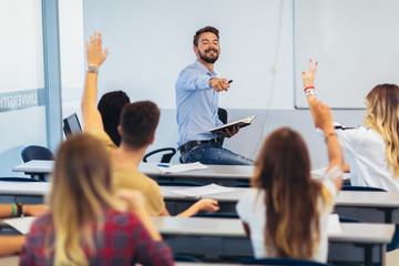 Group of students raising hands in class on lecture