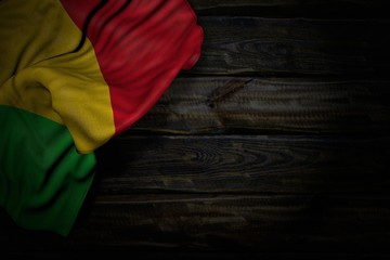 pretty dark picture of Mali flag with big folds on old wood with empty place for text - any holiday flag 3d illustration..