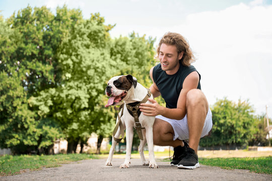 Sporty young man with cute dog in park