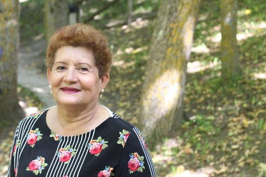 One Hispanic senior woman smiling outdoors