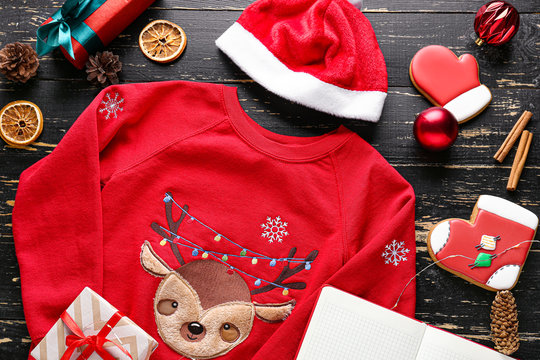 Christmas clothes with gift boxes and cookies on wooden background