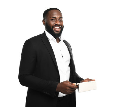 Handsome African-American businessman with mobile phone on white background