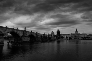 Prague, black and white art photo. Charles Bridge are the symbols of Czech capital, built in medieval times. Misty morning with storm clouds. Travelling in the Europe town.