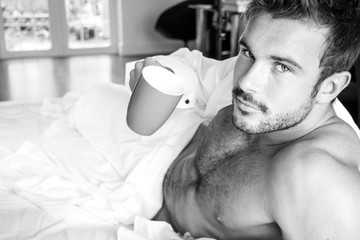 Handsome hairy naked muscular man with beard sixpack abs lying in bed covered with sheet drinking coffee