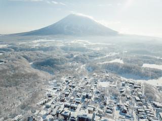 Winter in Niseko, Japan. A blue bird kind of day at Grand Hirafu, Niseko Ski Resort. Photos were taken with a drone overlooking the Grand Hirafu area with views of Mt. Niseko-Annupuri. and Mt. Yotei.