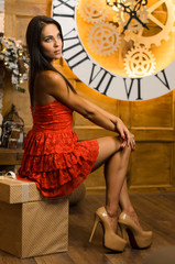 young attractive slim woman with straight hair in red evening dress with legs on high heels shoes is posing on background of large wall clock with roman numerals and gears indoors