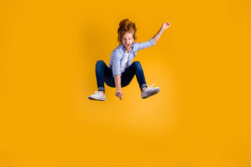 Full length body size photo of crazy ecstatic cheerful guy jumping up as high as possible wearing jeans denim blue shirt footwear isolated over vibrant color background
