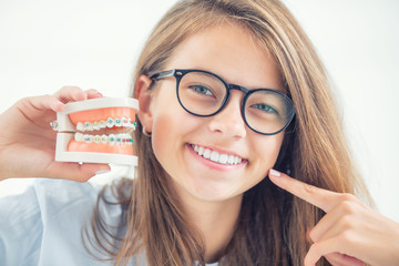 Model of a dental braces in the hand of a young girl with aligned teeth after the process of using a dental brace