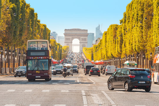 29 July 2019, Paris, France: Buses and cars drive along Avenue Champs Elysees with the Arc de Triomphe in the background