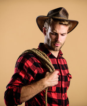 Western life. Man cowboy beige background. Man wearing hat hold rope. Ranch occupations. Lasso tool of American cowboy. Lasso is used in rodeos part competitive events. Lasso can be tied or wrapped