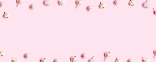 Harvest concept. Bulbs of garlic frame on a pink wooden background. Harvest concept. Top view. Flat lay.