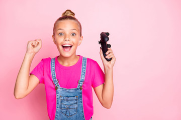 Photo of excited cute nice blonde preteen girl having won contests at video games celebrating victory wearing fuchsia t-shirt jeans denim isolated over pink pastel color background
