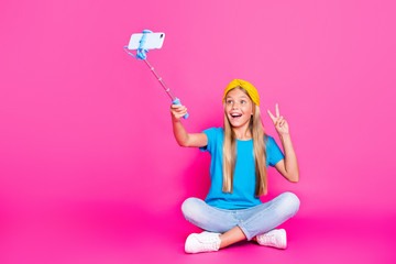 Full body photo of crazy kid blogger legs crossed on travel trip take selfie make v-signs recording video call wear blue t-shirt yellow headband denim jeans sneakers isolated pink color background
