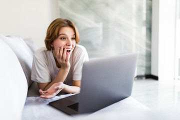 Young positive surprised girl sitting on couch in living room at home alone using laptop. Female looking at computer desktop with opened mouth unexpected great discounts offers, read news on internet