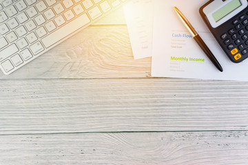Flat lay view of office workspace with keyboard, pen, paperwork on wooden background. Business concept and Copy space