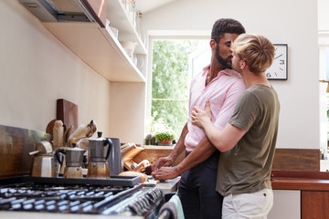 Loving Male Gay Couple At Home In Kitchen Making Breakfast Together