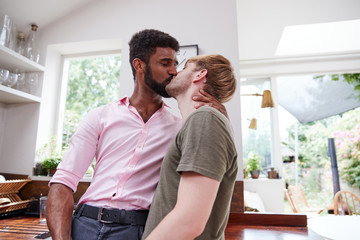 Loving Male Gay Couple Hugging And Kissing At Home In Kitchen