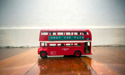 toy bus on a wooden floor with a message