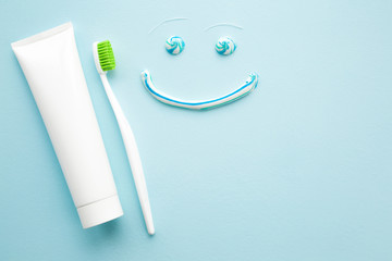 Toothbrush with green bristles, white tube of toothpaste on pastel blue background. Happy, smiley face created from paste. Healthy teeth concept. Empty place for text.