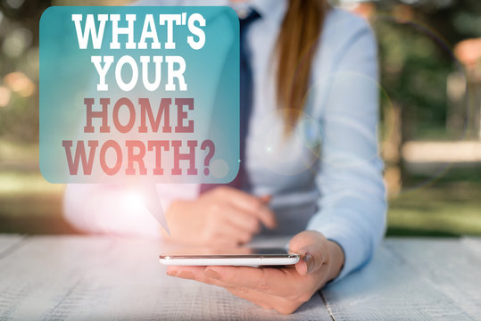Writing note showing What S Your Home Worth Question. Business concept for Value of a house Property Cost Price Rate Female business person sitting by table and holding mobile phone