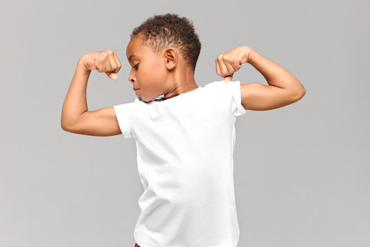 Children, fitness and bodybuilder concept. Studio shot of athletic muscled African American boy in casual t-shirt demonstrating strength by tensing bicep muscles, having proud confident look