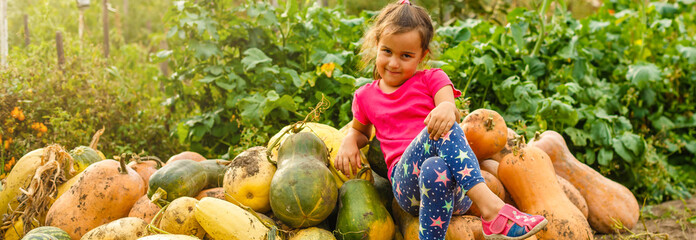Little girl with pumpkin outdoor having fun in autumn park.