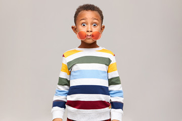 Oops. Funny bug eyed dark skinned little boy in stylish multicolored jumper staring at camera in full disbelief, round pink sunglasses slipped off his eyes. Surprise, shock and astonishment