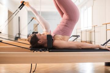Two women doing reformer pilates exercise.