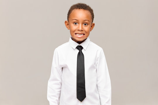 Shy or scared emotional African schoolboy in white shirt and black tie baring his teeth. Portrait of funny dark skinned child in formal clothes grimacing against blank studio wall background