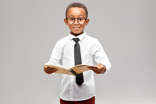 Studio image of funny smart akward African schoolboy in formal clothes and eyeglasses eager to learn, holding open book in his hands and smiling. Enthusiastic dark skinned A-student learning at school