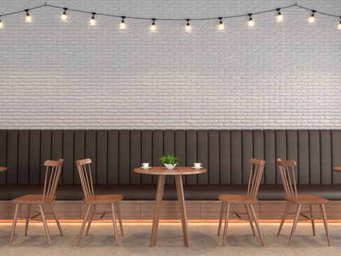 Loft style coffee shop with white brick walls decorated with brown leather benches and tables, wooden chairs adorning the walls with string lights.3d render