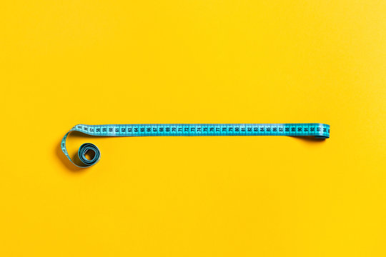 Diet concept, tape measure on yellow background.