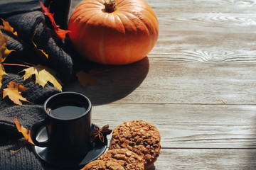 Grey cup of coffee, stack of cookies, spices, scarf, yellow maple leaves, orange pumpkin on white wooden table. Autumn menu concept. Fall, expresso, cinnamon